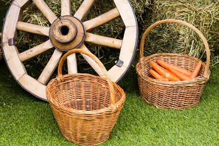 lug: The village concept. Baskets with carrots and a cart from a cart near the hay. Stock Photo