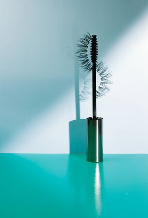 Applicator mascara and false eyelashes with drop shadow on sea-green background