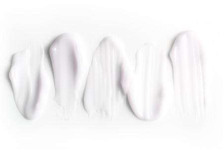 Eine Gruppe von strukturierten Strichen von Feuchtigkeitscremes auf weißem Hintergrund. Standard-Bild