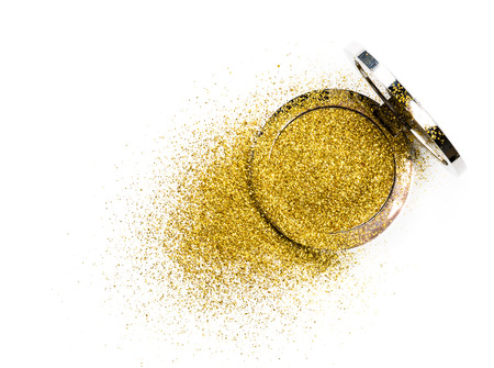 Powder highlighter in a silver powder box with gold sparkles reflected in the mirror. Isolated on white background.