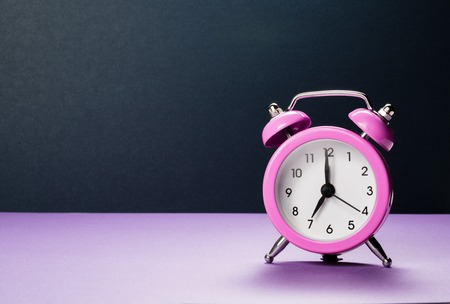 Pink alarm clock at seven oclock in the morning on a purple background.