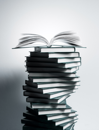 A spiral of stacks of books in the form of DNA and an open textbook at the top. 免版税图像