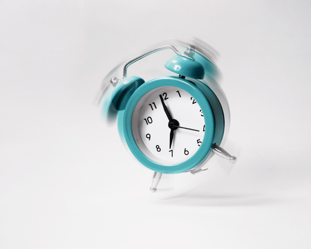 The blue morning alarm rings and jumps on a gray background. Banco de Imagens