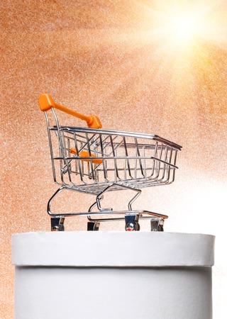 Orange shopping trolley on a round white gift box on a warm sunny summer shiny background with sunshine.