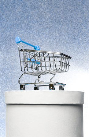 Shopping trolley on a round white gift box on a winter blue shiny background.