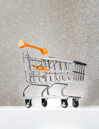 Trolley for shopping on a pedestal on a silver background with a glow. Best Buyer, Best Buy.