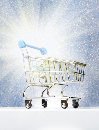 Trolley for shopping on a pedestal on a winter blue background with a glow. Best Buyer, Best Buy.