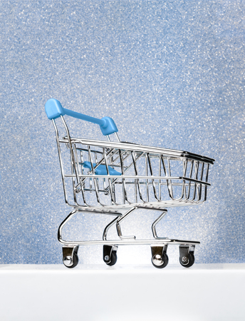 Trolley for shopping on a pedestal on a winter blue background. Best Buyer, Best Buy.