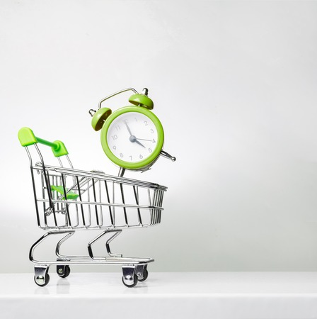 Alarm clock and shopping trolley with space for text. Time to shop.