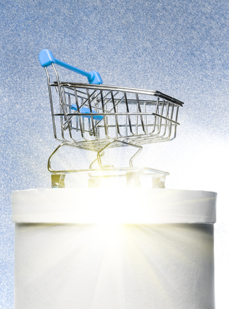 Shopping trolley on a round white gift box on a winter blue shiny background with bright rays.