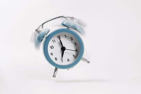 The blue morning alarm rings and jumps on a gray background. Stock Photo