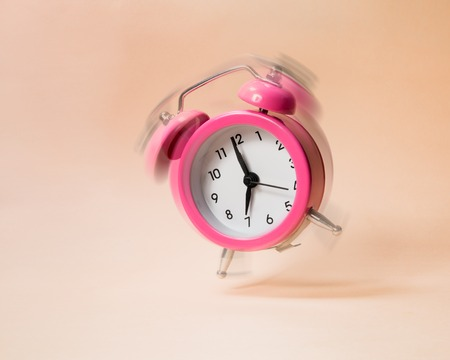 Pink bouncing ringing alarm clock on a beige background. Motion blur.