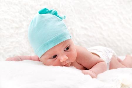 El bebé tranquilo mira hacia un lado, se acuesta en suaves almohadas blancas Foto de archivo