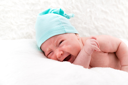 Crying newborn baby without clothes and in a cap on white pillows.