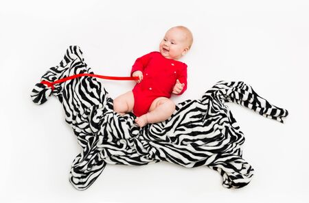 a four-month-old child rides a Zebra from a cloth on the floor