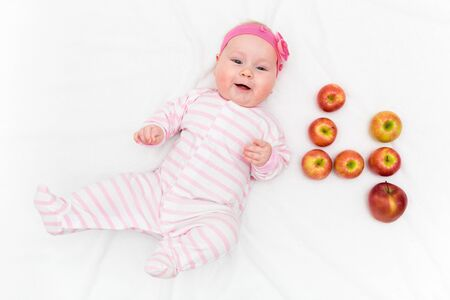 Cute little baby girl laying on white background with fresh red-green apples in shape of number four Banco de Imagens