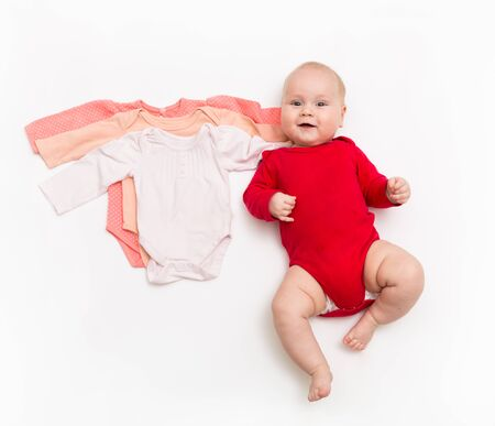 A four month happy baby in red bodysuit lying on a white background with pink clothes smaller size.