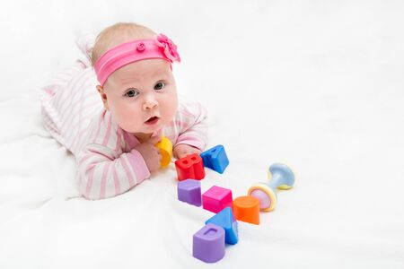 Cute baby playing with colorful toy. New born child, little girl looking at the camera and crawling. figure four of the toy cubes Banco de Imagens