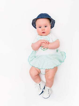 Happy cute 4 months old smiling baby in jeans hat on a white background.