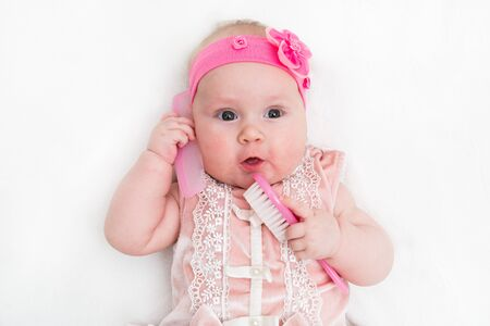 Cute little baby playing with a hairbrush on white background