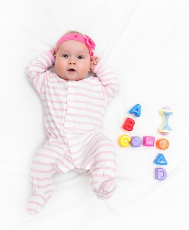 Cute baby playing with colorful toy. New born child, little girl looking at the camera and lying. Baby learning grab. figure four of the toy cubes