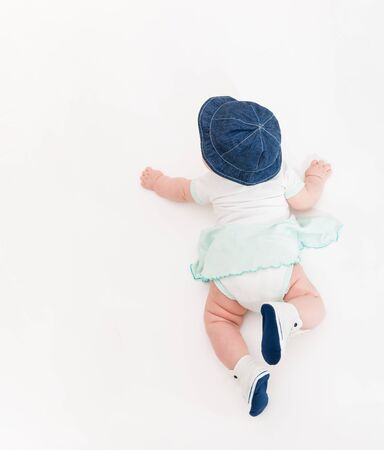 Crawling Baby on white Background in jeans hat and bootees, Infant Kid Top View