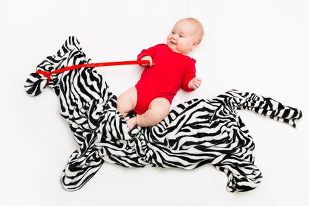 Funny cute baby sitting on the toy horse or zebra and smiling Banco de Imagens