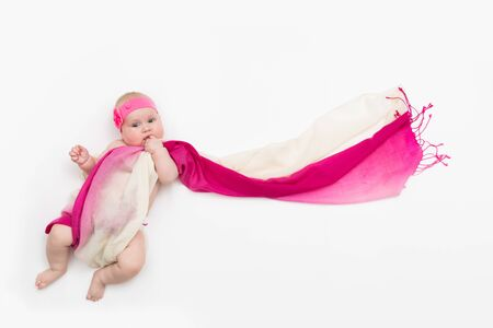 Child lying on white background wrapped in long fabric