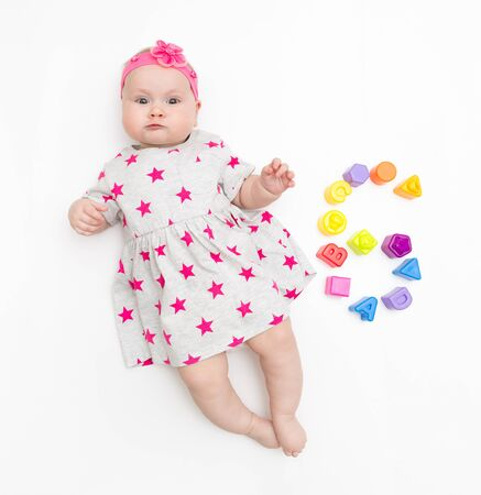 Portrait of a sweet infant baby girl wearing a pink dress and headband bow, isolated on white in studio with number six from toys