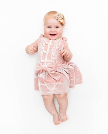 Portrait of a sweet infant wearing a pink dress, headband bow, isolated on white in studio.