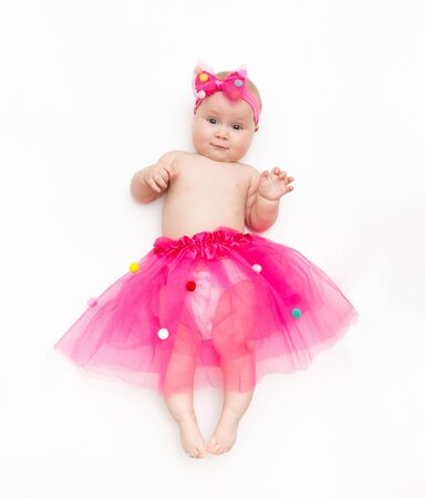 Portrait of a sweet infant wearing a pink tutu and headband bow, isolated on white