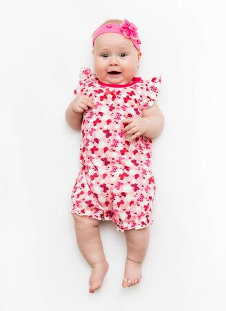 Portrait of a sweet infant baby girl wearing a pink dress and headband bow, isolated on white in studio Foto de archivo