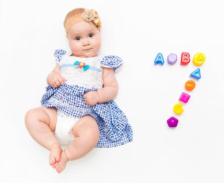 Portrait of a sweet infant baby girl wearing a pink dress and headband bow, isolated on white in studio with number seven from toys