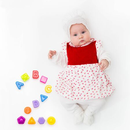 Portrait of a sweet infant baby girl wearing a red dress and bonnet, isolated on white in studio with number two from toys