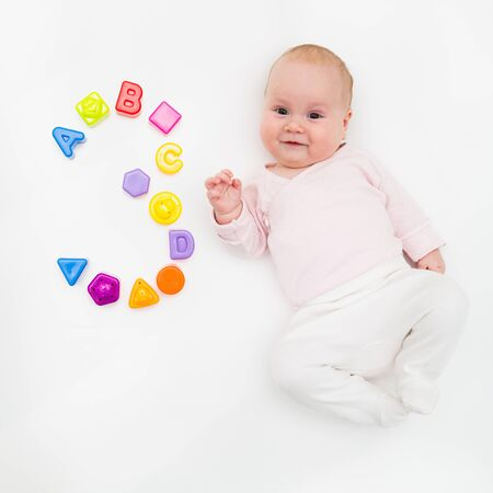Portrait of a sweet infant baby girl wearing a red dress and bonnet, isolated on white in studio with number tree from toys, cubes, letters and molds