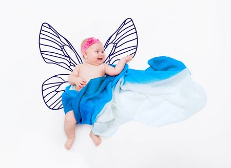 Laughing baby girl wrapped in fabric on cloud with painted butterfly wings
