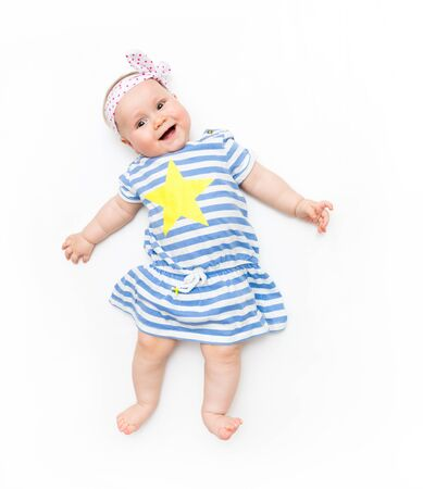 Cute baby girl lying on a white background wearing wearing a striped dress with a big yellow star