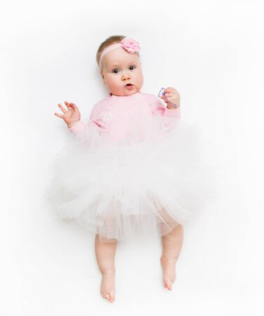 Portrait of a sweet infant wearing a pink tutu and headband bow, isolated on white in studio