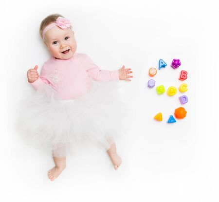 Portrait of a sweet infant baby girl wearing a pink dress and headband bow, isolated on white in studio with number nine from toys.