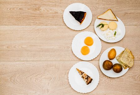 Healthy breakfast with pie, omelet, pancakes, jelly, cottage cheese, pie, muffin, cheesecake, sandwich on white plates. View from above on wooden table with copy space