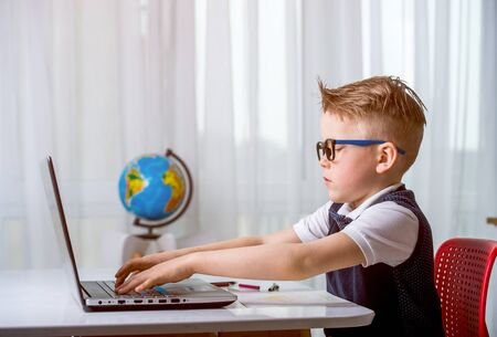 Child using a laptop computer while doing homework online on laptop. Pupil in headphones. Learn English. Reklamní fotografie