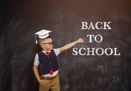 Smart kid boy in uniform. Hero child with education cap against blackboard Stockfoto