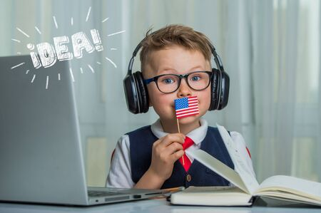 Back to school. Thinking child doing homework online with flag. Pupil in headphones. Learn English online