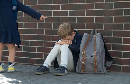 school bully. Kid boy sitting near wall and cry because of bullying.
