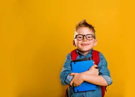 happy kid holding or hugging a big book over yellow background. Back to school