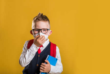 Portrait of of School kid wearing protective face mask for pollution or virus, Child in school uniform wearing medical face mask. Kid in uniform. Back to school