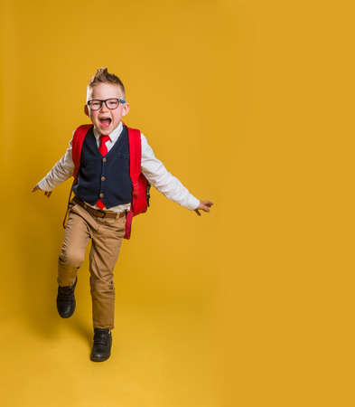 American school boy jumping , isolated on yellow background. School kid in uniform and glasses. Smart and nerd pupil Stock Photo