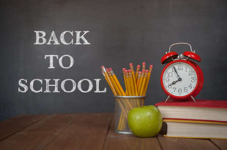 Desk, alarm clock, apple, pencils and school books against blackboard with back to school on background. Education