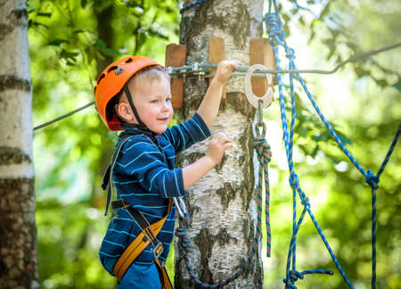 Little boy climbing in adventure activity park with helmet and safety equipment. Happy kid face Reklamní fotografie