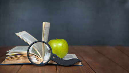 Green apple over pile of books over blackboard. Back to school concept
